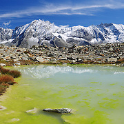 "Bright yellow algae grows in a tarn (mountain pond) which reflects peaks of Dents des Veisivi (left) and Aiguilles de la Tsa (right) above Arolla Valley, part of Val d'Hérens, in Valais (Wallis) Canton, Switzerland, Europe. Hike the High Route (Chamonix-Zermatt Haute Route) for classic mountain scenery. Panorama stitched from 2 images. Published in Ryder-Walker Alpine Adventures ""Inn to Inn Alpine Hiking Adventures"" Catalog 2006-2009, 2011."