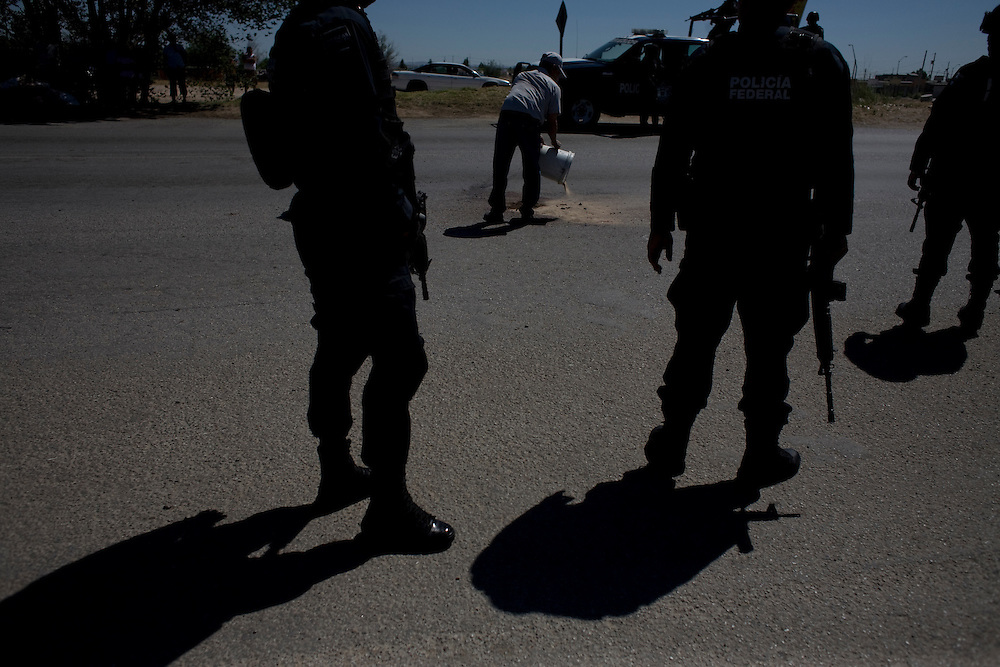 A man pours dirt onto the blood stain of a family member as Federal Police look on in Ciudad Juarez, Chihuahua on May 19, 2010.