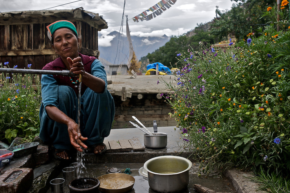 A Kinnauri woman in the village of Giabong in the Ropa Valley of Himachal Pradesh, India, runs water from a faucet as she prepares to wash her dishes