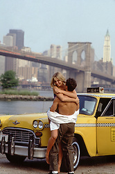 passionate couple in New York City by an antique taxi cab