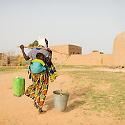 A woman carrying two heavy containers of water home from a well refurbished by WaterAid in the village of Gadirga in the Commune of Soukoukoutan in the Dosso Region of Niger on 23 July 2013.