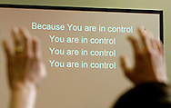 A worshiper holds up his hands with the lyrics to a song on the screen in the background at the Sunday church service at Tried-Stone Christian Center in Blacksburg, Virginia April 22, 2007.  The church has members that were directly affected by the shooting tragedy. REUTERS/Rick Wilking (UNITED STATES)