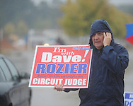 Dave Rozier holds a campaign sign as voters go to the polls in the rain at the Oxford Conference Center in Oxford, Miss. on Tuesday, November 2, 2010.