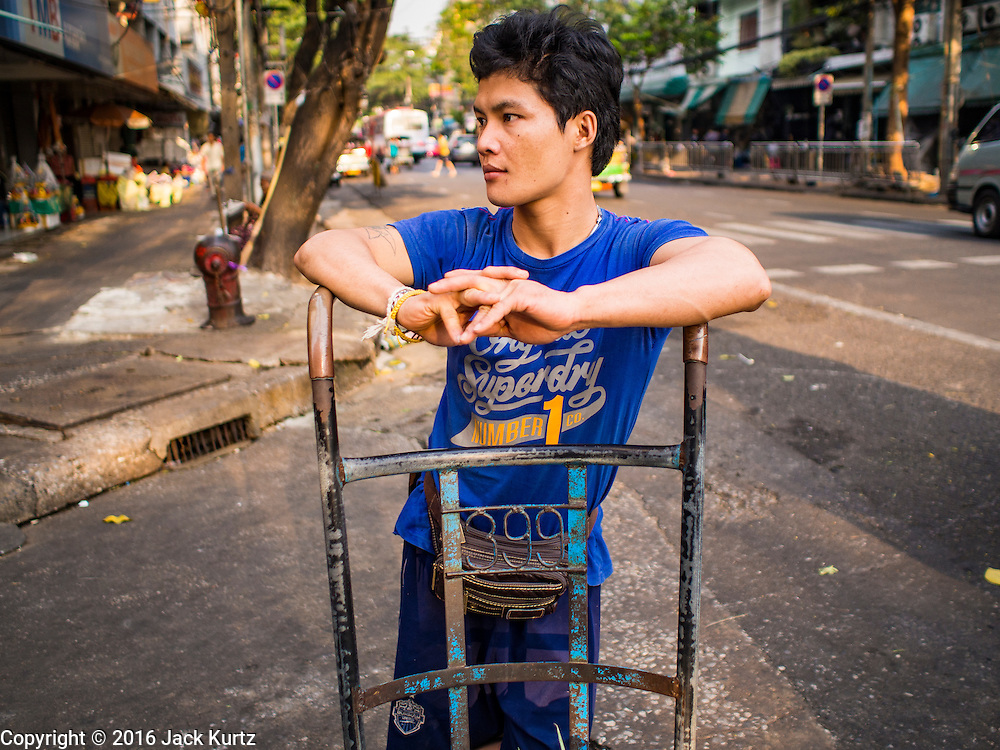 29 FEBRUARY 2016 - BANGKOK, THAILAND: A porter waits for business in front of the Bangkok flower market. The sidewalk behind him used to be crowded with flower vendors. Many of the sidewalk vendors around Pak Khlong Talat, the Bangkok flower market, closed their stalls Monday. As a part of the military government sponsored initiative to clean up Bangkok, city officials announced new rules for the sidewalk vendors that shortened their hours and changed the regulations they worked under. Some vendors said the new rules were confusing and too limiting and most vendors chose to close Monday rather than risk fines and penalties. Many hope to reopen when the situation is clarified.    PHOTO BY JACK KURTZ