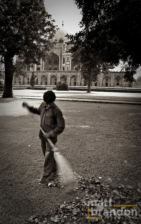 A black-and-white image of a man sweeping leaves in front of humayun's tomb.