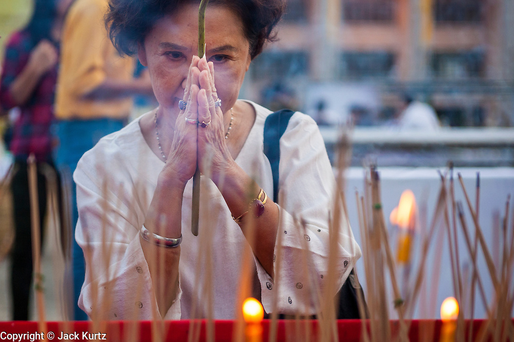 13 APRIL 2014 - BANGKOK, THAILAND: A woman prays during a Songkran ceremony at Bangkok City Hall. Many people go to temples and religious ceremonies to make merit on Songkran. Songkran is celebrated in Thailand as the traditional New Year's Day from 13 to 16 April. Songkran is in the hottest time of the year in Thailand, at the end of the dry season and provides an excuse for people to cool off in friendly water fights that take place throughout the country. Songkran has been a national holiday since 1940, when Thailand moved the first day of the year to January 1.    PHOTO BY JACK KURTZ