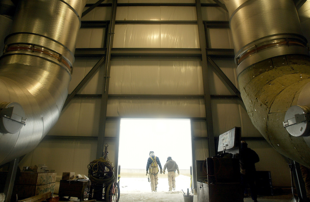 Fagen workers walk out of the process center under dryer vents Monday, December 15, 2003, where the corn, which has had the starch removed to create ethanol, is dried for the distilled dry grain and sold as feed. The process produces 16 pounds of feed additive per bushel of corn, which weighs 56-pounds.