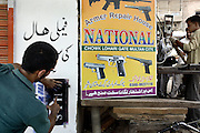 Celebrated young pakistani artist Asim Butt on a journey of political graffiti through Pakistan during the summer of 2009..Making the piece 'For the waste alone' in the gun market in central Multan