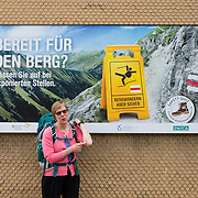"""Ready for the mountain? A backpacker points to an imagined elbow owie. """"Mountain Hiking - but Safe"""" campaign (sponsored by SWICA, one of Switzerland's leading health and accident insurers): www.sicher-bergwandern.ch. Lauterbrunnen village is in the canton of Bern, Switzerland, the Alps, Europe. For licensing options, please inquire."""