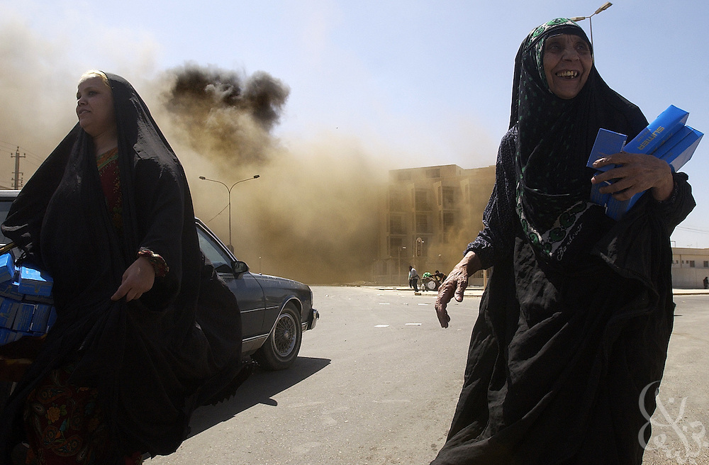 Iraqi women carry loads of looted cigarettes April 11, 2003 in Baghdad, Iraq. Widespread looting of both government buildings and private businesses was rampant across Baghdad following the collapse of local authority after coalition forces took the city.