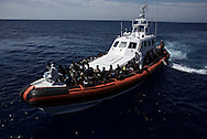 Italy: MSF Dignity1: Migrants rescued at sea on an Italian coastal guard boat as it approaches the Dignity1 to be transferred on it on August 23, 2015. Alessio Romenzi