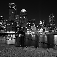 Boston Black and white photography of the famous Boston Harbor skyline as seen from Fan Pier, part of the Harbor Walk. This historic and iconic New England city of Boston night scenery photography image is available as museum quality photography prints, canvas prints, acrylic prints or metal prints. Fine art prints may be framed and matted to the individual liking and decorating needs:<br />
