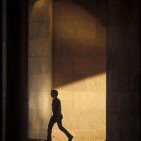 A man walks through the arches in Federal Triangle in Washington, DC.