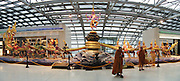 "Buddhist monks stand by the impressive sculpture of the Churning of the Milk Ocean. The artwork was relocated elswhere in 2008 as it was too big (30 meters wide and 5.5 meters high) for the fire regulations of Suvarnabhumi Bangkok Airport (pronounced ""Su-Wana-Poom"" in Thai, meaning ""The Golden Land""). The Churning of the Milk Ocean (or Sagar Manthan; Samudra Manthan; Samudra manthanam; or Ksheersagar manthan) is one of the most famous episodes in Sanskrit literature, appearing in the Srimad Bhagavatam, the Mahabharata and the Vishnu Purana. Demons and gods cooperate to churn the sea for thousands of years in order to bring forth missing treasures after the recreation of the universe, including the heavenly nectar of immortality (amrita). The King Power Group donated this 48-million-baht art sculpture to the Airport. Image published 2010 by Institute of Southeast Asian Studies (ISEAS), Singapore. Panorama stitched from 2 overlapping images."
