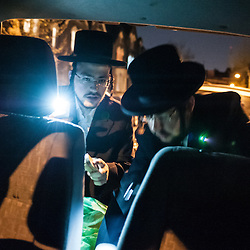 London, UK - 13 April 2014: Levi and Yaakov Schapiro of the Jewish Community of Stamford Hill search for chametz (leavened bread products) in their car on the night before Passover.