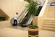 A man cleans the escalator handrail at the newly-renovated Basrah International Hotel on Friday, October 22, 2010 in Basrah, Iraq.