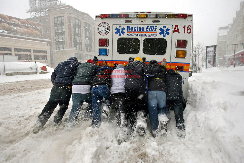 """""""Final Push""""  A city of Boston ambulance is freed from the snow by people who were passing by as the quick Blizzard continued this morning."""