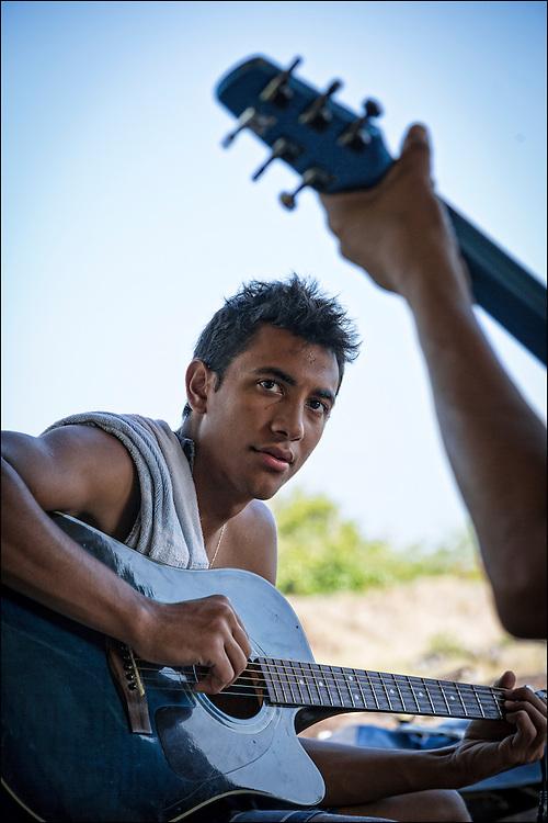 At the Keawanui Fishcamp, Kai Kahoaliki Fonseca checks cords as Brother Nolan plays.