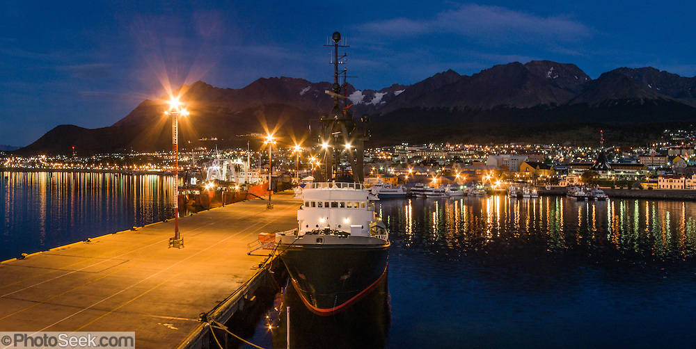 """At dawn, lights reflect in the Beagle Channel at the Port of Ushuaia, capital city of Tierra del Fuego Province, Argentina, South America. As the port closest to Antarctica (which is located 400 miles across the Drake Passage), Ushuaia hosts most of the cruise ships that visit the southernmost continent. Argentina claims Ushuaia is the """"southernmost city in the world"""" (although the smaller Chilean town of Puerto Williams lies further south). The Martial Mountains provide skiing and hiking above town. Panorama was stitched from 3 overlapping photos."""