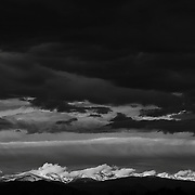 SHOT 10/19/09 9:11:59 AM - Some of the mountain peaks with dark clouds lingering above the Front Range just outside of Thornton, Co. The Front Range is a mountain range of the Rocky Mountains of North America that is located in the north-central portion of the U.S. State of Colorado. The Front Range is so named because, moving west along the 40th parallel north across the Great Plains of North America, it is the first mountain range encountered. This setting provides both scenery as the Front Range towers over Denver and Boulder and is an outdoors hotspot for the people living there who take part in mountain biking, hiking, climbing, camping, skiing, and snowboarding during winter. (Photo by Marc Piscotty / © 2009)