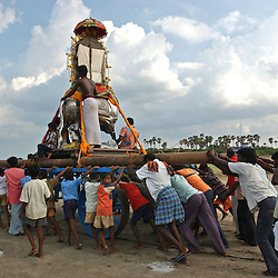 """Holy men and fishing families from New beach in Nagapattinum district in Tamil Nadu, India carry an idol of the God of the Sea, Athi Baktha Navanar from the ocean as they take part in the unique ritual of reliving the day when Athi Baktha Nayanar found a gold fish in the ocean, offered it to his God and received """"moksha"""", September 2,2005. Villagers worship this God who is know to be the God of the Sea and the 49th nayanmar. The yearly ritual symbolizes an unwavering  pious man who always offered his daily catch to his God first, even when people in his village were starving. The ritual had been stopped for 25 years and many fishermen believed this is why the tsunami ravaged the coast of India.  (Ami Vitale)"""