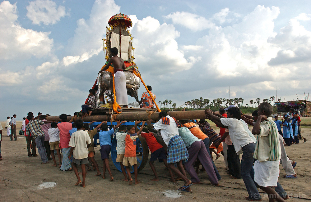 "Holy men and fishing families from New beach in Nagapattinum district in Tamil Nadu, India carry an idol of the God of the Sea, Athi Baktha Navanar from the ocean as they take part in the unique ritual of reliving the day when Athi Baktha Nayanar found a gold fish in the ocean, offered it to his God and received ""moksha"", September 2,2005. Villagers worship this God who is know to be the God of the Sea and the 49th nayanmar. The yearly ritual symbolizes an unwavering  pious man who always offered his daily catch to his God first, even when people in his village were starving. The ritual had been stopped for 25 years and many fishermen believed this is why the tsunami ravaged the coast of India.  (Ami Vitale)"