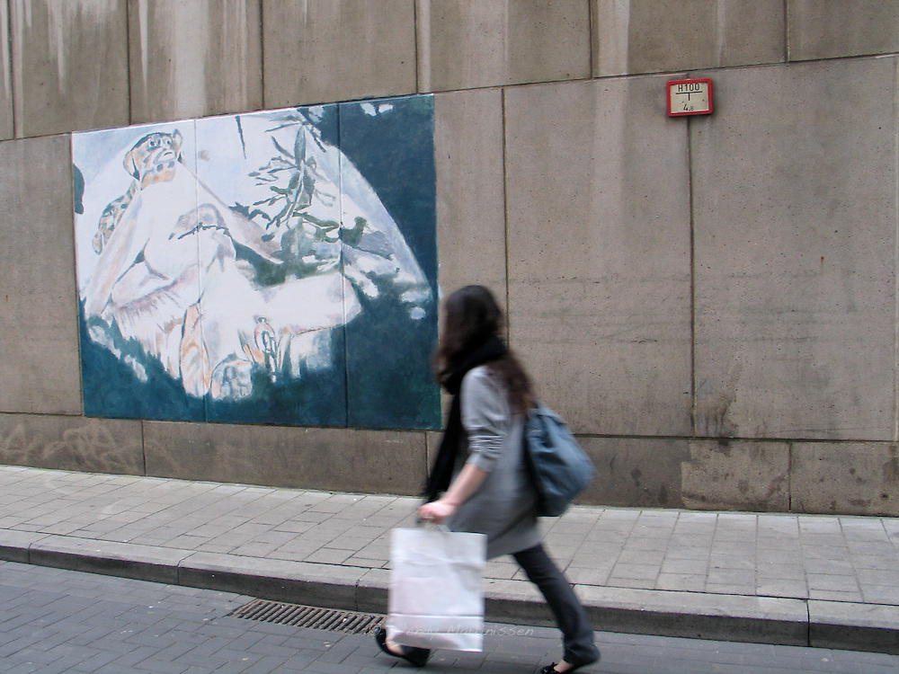 A young woman walks past a temporary painting by Belgian artist Luc Tuymans. Antwep, Belgium