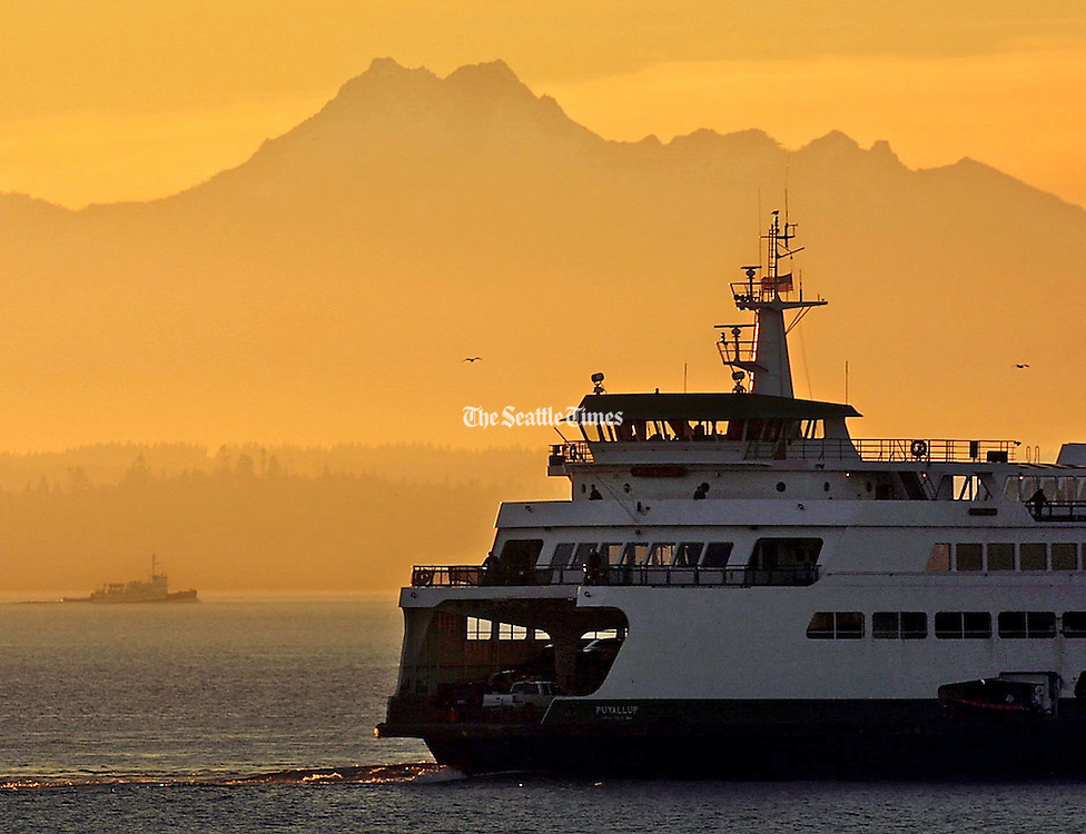 Haze in the atmosphere over Puget Sound created a colorful sunset over the Olympic Mountains and the ferries running between Edmonds and Kingston. (Harley Soltes / The Seattle Times)
