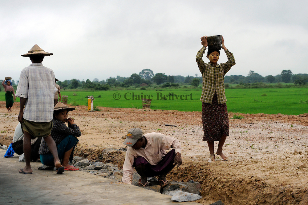 """Burmese workers forced to work on the Naypyidaw highway. Men, women, even children, whole families are called up to achieve what the junta calls Working for the country"""". They are compelled to work from sunrise to nightfall watched by guards, under strict surveillance."""