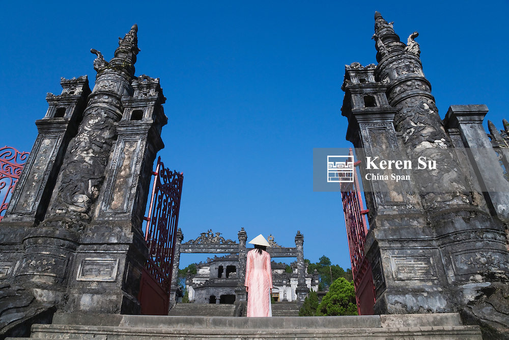 Girl in Ao Dai (traditional Vietnamese long dress) and conical hat at Tomb of King Khai Dinh.