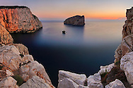 A view at sunset of the huge vertical walls of limestone of the cliffs of Capo Caccia, a wonderful promontory on the western coast of Sardinia in Italy. with the beautiful small Island of Foradada in the background. Taken on a beautiful evening of September about 10 minutes before sunset.