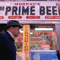 An elderly man walks past a New York City deli in the Lower East Side of Manhattan.