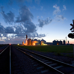 Summer storm clouds gather over the northern Illinois plains and a giant grain elevator complex near DeKalb. A railroad main line passes in the foreground, including a crossing warning device.