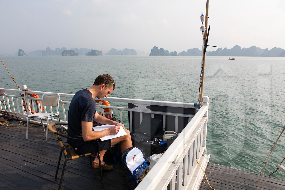 A scientist sits on a deck in Halong Bay taking notes while conducting a black carbon study, Quang Ninh Province, Vietnam, Southeast Asia