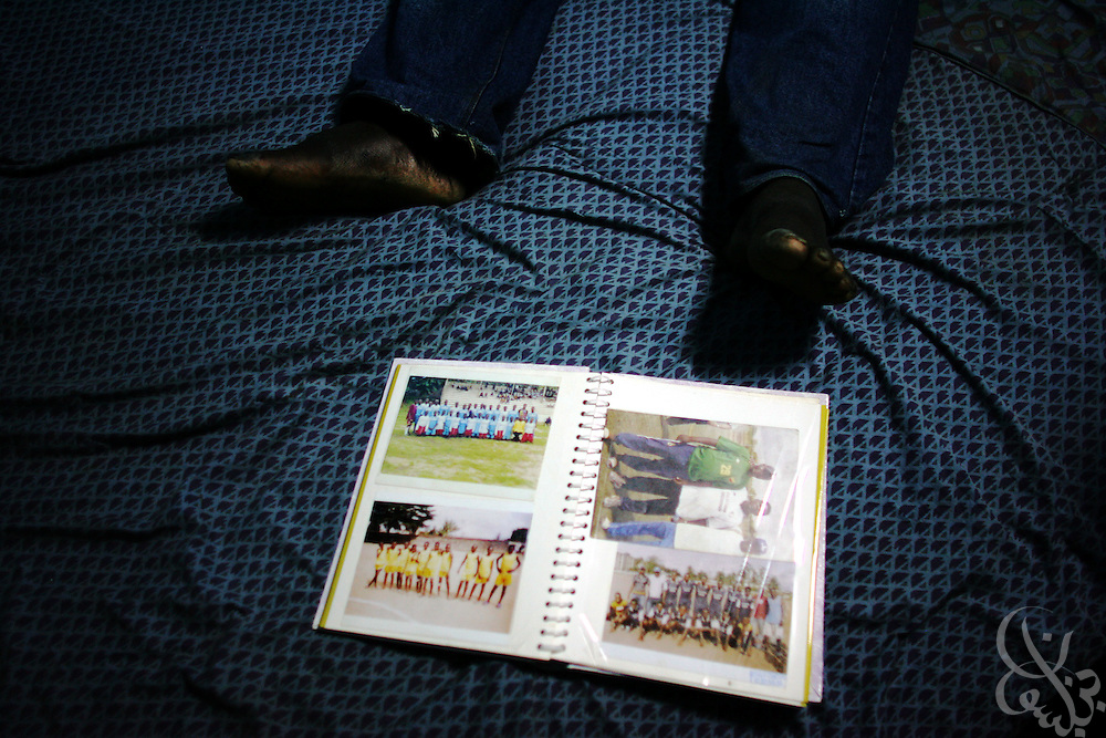 A football scrapbook lies at the feet of Amza Sylla, age 26, amid his foootball decorated room in the Abobo neighborhood of Abidjan, Côte d'Ivoire February 18, 2006. Sylla is the founder and director of the Olympic Sport Abobo club one of more than 300 football academies have arisen in Abidjan, amid the success of the ASEC academy.  Sylla also acts as a scout of local football talent for ASEC directors and earns the equivalent of 10 U.S. dollars per player that he recruits for the academy.