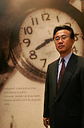 MINORU HATAGUCHI: Director of the Hiroshima Peace Museum lost his father in the bombing, standing in front of the picture of the clock that stoped on the time of the bombing.  His mother was two months pregnant when the bomb fell.  She went looking for her husband who worked at a railway station.  She found his watch, which Hataguchi keeps in a glass case in his office to remind him of what happened.