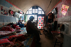 Chinese 'yaodong' or cave home dwellers Bei Fenglan sits in her 'yaodong' or cave home with her grandson Wang Xi in Yichuan county of Yan'an city, Shaanxi Province China, 06 November 2012. Bei's family of six are apple farmers and have seen growing difficulties in making ends meet from their produce, prompting her 38-year-old son to leave home to work as a construction worker to help support the family. The 'yadong' or cave dwellings are typical in the plateaus of northern China in Shaanxi Province where many of Yan'an's rural population still live in. They are mostly carved out from the yellow earth of the Loess hillsides and are about seven to eight metres deep with height and width of three metres. Former Communist leader Mao Zedong and his comrades are known to have hid in these cave homes during the civil war between the communists and nationalists in 1936 to 1948 as they battle the Kuomintang forces. China's new leaders slated to take over during the 18th National Congress beginning on 08 November are likely to face mounting pressures to tackle the country's rising income inequalities between urban and rural areas that are often the source of simmering resentment and growing unrests on the grassroot level.