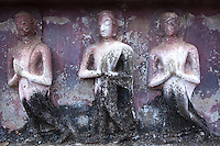 Bas Relief Buddha Disciples at Wat Mahathat which is made up of over 200 buildings and structures. Wat Mahathat was founded around the middle of the thirteenth Century by the Thai King Sri Intaratit.