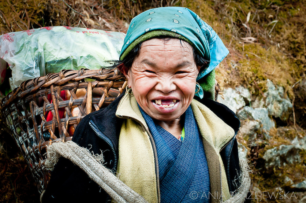 Nepal, Himalayas. Portrait of a smiling Sherpa woman with a basket.