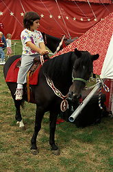 "Circus pony ride for children. Bentley Bros. circus, one of the few remaining ""mud show"" circus performing under a canvas big top."