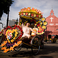 Tourist posing in trishaws at the square in front of Christ Church