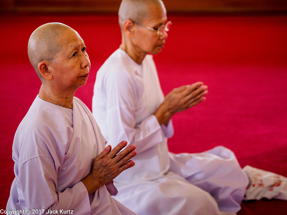 """11 APRIL 2017 - BANGKOK, THAILAND: Buddhist nuns pray in Wat Chana Songkhram during a Songkran merit making service. Songkran is the traditional Thai Lunar New Year. It is celebrated, under different names, in Thailand, Myanmar, Laos, Cambodia and some parts of Vietnam and China. In most places the holiday is marked by water throwing and water fights and it is sometimes called the """"water festival."""" This year's Songkran celebration in Thailand will be more subdued than usual because Thais are still mourning the October 2016 death of their revered Late King, Bhumibol Adulyadej. Songkran is officially a three day holiday, April 13-15, but is frequently celebrated for a full week. Thais start traveling back to their home provinces over the weekend; busses and trains going out of town have been packed.     PHOTO BY JACK KURTZ"""