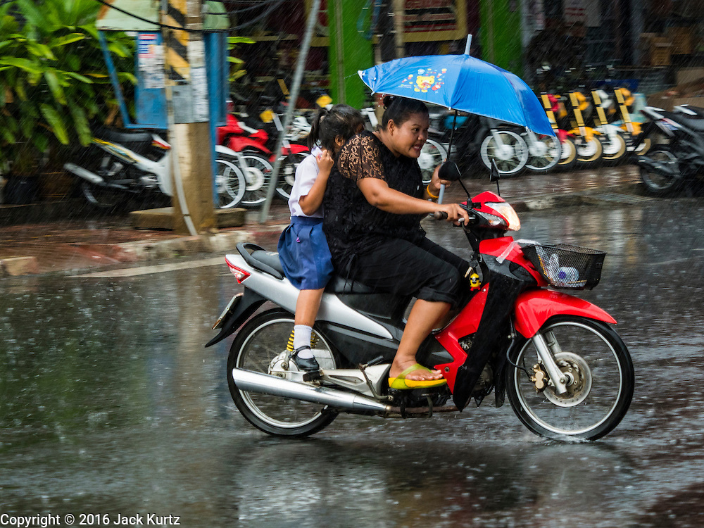 19 JANUARY 2016 - BURI RAM, BURI RAM, THAILAND: People on a motorcycle duck raindrops during an unseasonal thunderstorm in Buri Ram, Thailand.    PHOTO BY JACK KURTZ