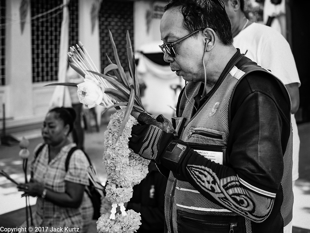 """11 APRIL 2017 - BANGKOK, THAILAND: A motorcycle taxi driver prays at Wat Chana Songkhram in Bangkok during a Songkran merit making service. Songkran is the traditional Thai Lunar New Year. It is celebrated, under different names, in Thailand, Myanmar, Laos, Cambodia and some parts of Vietnam and China. In most places the holiday is marked by water throwing and water fights and it is sometimes called the """"water festival."""" This year's Songkran celebration in Thailand will be more subdued than usual because Thais are still mourning the October 2016 death of their revered Late King, Bhumibol Adulyadej. Songkran is officially a three day holiday, April 13-15, but is frequently celebrated for a full week. Thais start traveling back to their home provinces over the weekend; busses and trains going out of town have been packed.     PHOTO BY JACK KURTZ"""