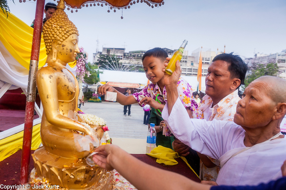 13 APRIL 2014 - BANGKOK, THAILAND:  A Buddhist nun and others bathe a Buddha statue in scented oils at Bangkok City Hall. Many people go to temples and religious ceremonies to make merit on Songkran. Songkran is celebrated in Thailand as the traditional New Year's Day from 13 to 16 April. Songkran is in the hottest time of the year in Thailand, at the end of the dry season and provides an excuse for people to cool off in friendly water fights that take place throughout the country. Songkran has been a national holiday since 1940, when Thailand moved the first day of the year to January 1.   PHOTO BY JACK KURTZ