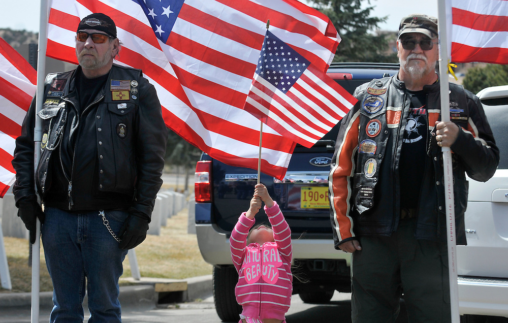em032613i/jnorth/daily/Mia Garcia, 3, holds a flag between her grandfather Cliff Garcia, right, from Bosque Farms, and Dennis Hawley, left, from Los Alamos, as they and other members of the Patriot Guard attend an interrenment ceremony for 6 veterans at the Santa Fe National Cemetery, in Santa Fe, Tuesday, March 26, 2013. Mia's father Francisco Garcia is serving his 5th tour now in Kuwait. (Eddie Moore/Albuquerque Journal)