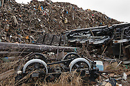Mountains of debris and garbage caused by the 2011 tsunami, sit beside a steam locomotive which has been swept off it's pedestal/foundations, on the 1 year anniversary of the March 11th 2011 earthquake and tsunami, in Minami-Sanriku, Tohoku region, Japan on Sunday 11th March 2012.
