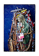 "SHOT 1/31/10 1:47:52 PM - Rosaries and pictures of loved ones adorn a Virgin Mary high atop a hillside near Ciudad Obregon, Mexico along Highway 15. The site is a popular destination to leave well wishes and thanks by family members. The Virgin of Guadalupe has symbolized the Mexican nation since Mexico's War of Independence. Our Lady of Guadalupe (Spanish: Nuestra Señora de Guadalupe) is a celebrated Catholic icon of the Virgin Mary also known as the Virgin of Guadalupe (Spanish: Virgen de Guadalupe). The Lady of Guadalupe is of significant importance to Mexican Catholics and has been given the titles of ""Queen of Mexico"", ""Empress of the Americas"", and ""Patroness of the Americas"". Roadside capillas, or tiny chapels, in the Mexican states of Nayarit, Sinaloa and Sonora. The capillas are common along the roads and highways of Mexico which is heavily Catholic and are often dedicated to certain patron saints or to the memory of a loved one that has passed away. Often times they contain prayer candles, pictures, personal artifacts or notes. (Photo by Marc Piscotty / © 2010)"