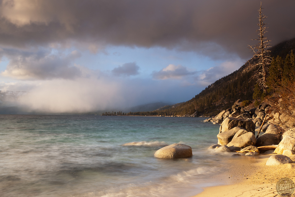 """Lake Tahoe Shoreline"" - Photograph of a distant snow shower happening over Lake Tahoe, shot from a beach just North of the Thunderbird Lodge."