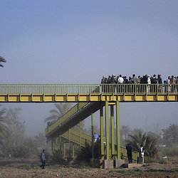 While dust is kicked up from UN employees being airlifted from the site, soldiers block the foot bridge as people try to get to the UN base at the Canal Hotel where a cement truck packed with explosives detonated outside the offices killing 20 people and devastating the facility in Baghdad, Iraq on Aug. 19, 2003. This was an unprecedented suicide attack against the world body with at least 100 people wounded.